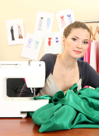 beautiful young dressmaker in workroom photo