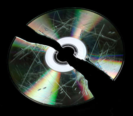 compromising: Defective and broken disk with information isolated on black Stock Photo