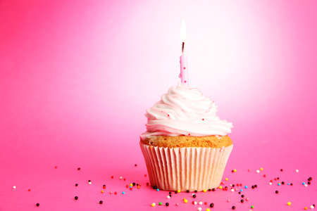 cake with icing: tasty birthday cupcake with candle, on pink background