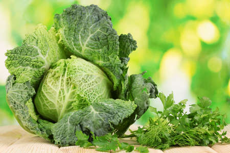Fresh savoy cabbage on wooden table on natural background photo