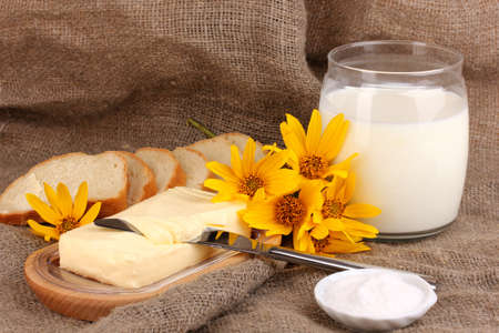 Butter on wooden holder surrounded by bread and milk on sacking background Stock Photo - 17144390