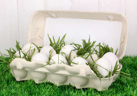 eco-friendly eggs in box on green grass on wooden background Stock Photo - 17143600