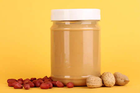 Delicious peanut butter in jar of peanut near on yellow background photo