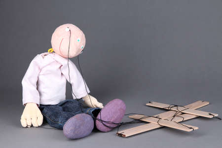 Wooden puppet sitting on grey background Stock Photo - 17144239