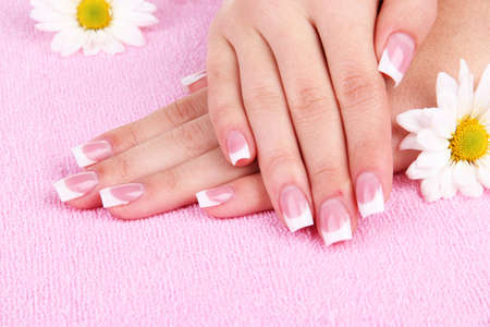 Woman hands with french manicure and flowers on pink towel photo