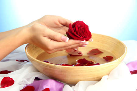 woman hands with wooden bowl of water with petals, on blue background Stock Photo - 17140752