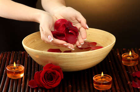 woman hands with wooden bowl of water with petals, on brown background Stock Photo - 17140910