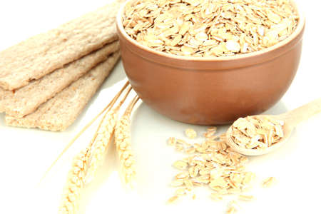 Brown bowl full of oat flakes with spikelets, oat biscuits and wooden spoon isolated on white photo