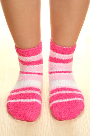 Legs female in striped socks on laminate floor photo