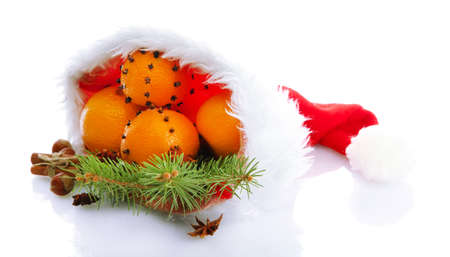 christmas composition with oranges and fir tree in Santa Claus hat, isolated on white photo