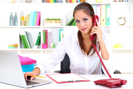 Young pretty business woman with phone and notebook working at office Stock Photo - 17263147