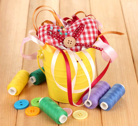 Color bucket with multicolor ribbons and thread on wooden background Stock Photo - 17140994
