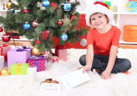 Little boy in Santa hat with milk, cookies and letter for Santa Claus photo