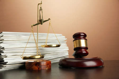 Golden scales of justice, gavel and folders on brown background photo