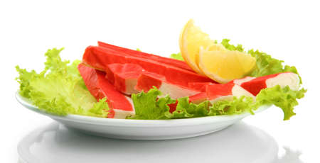 Crab sticks with lettuce leaves and lemon on plate isolated on white Stock Photo - 17139717