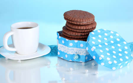 nutritiously: Chocolate cookies with creamy layer and cup of coffe on blue background Stock Photo