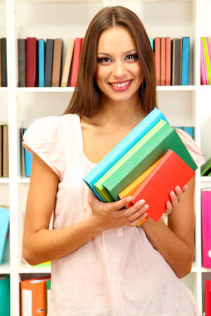 Young attractive female student holding her school books in library Stock Photo - 17282002
