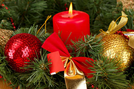 Christmas composition  with candle and decorations in red and gold colors on wooden background photo