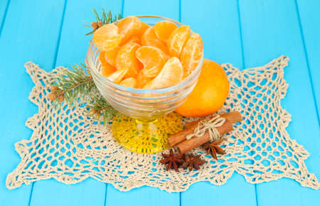 Tasty mandarines slices in glass bowl on blue background photo