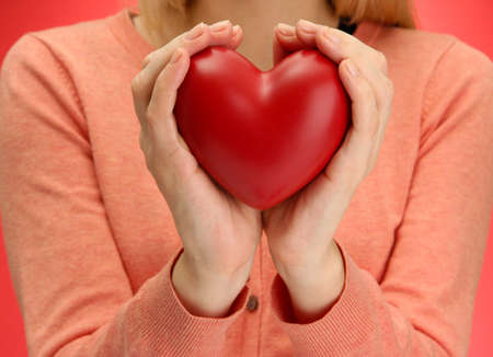 Red heart in woman hands, on red background photo