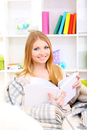 Attractive young woman sitting on sofa and reading book, on home interior background photo