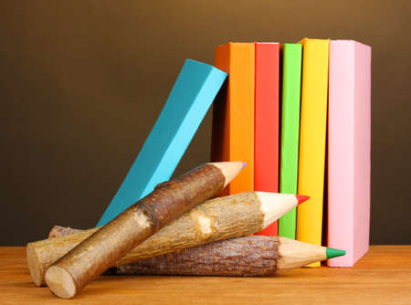 Colorful wooden pencils with books on wooden table on brown background photo