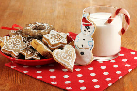 Christmas treats on plate and glass of milk on wooden table close-up photo