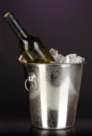 Bottle of wine in ice bucket on darck purple background photo