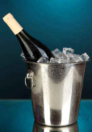 Bottle of wine in ice bucket on darck blue background photo