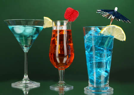 Alcoholic cocktails with ice on darck green background photo