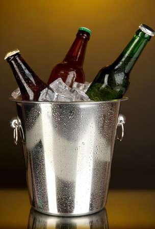 Beer bottles in ice bucket on darck yellow background Stock Photo - 17144233