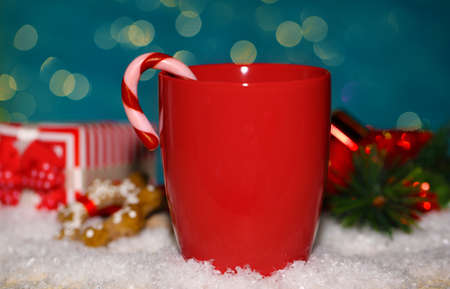 Hot tasty drink in red cup with Christmas candies on blue background photo