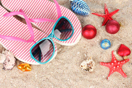Christmas balls,seashells andh beach accessories on sand, close-up photo