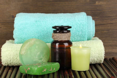 Bottle with aromatic oils with accessories for relaxation on wooden table on wooden background photo