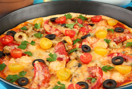 Delicious pizza with seafood in the frying pan close-up photo