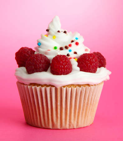 tasty cupcake with berries, on pink background photo