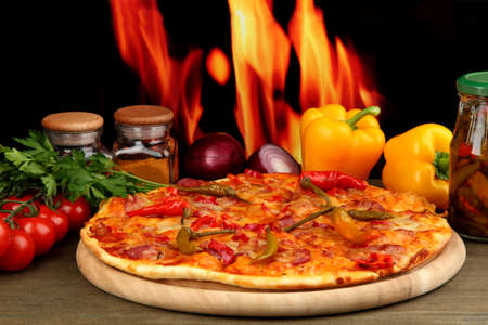 Tasty pepperoni pizza with vegetables on wooden board on flame background Stock Photo - 17215098