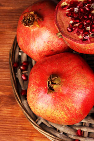 Ripe pomegranates on wicker cradle close-up photo
