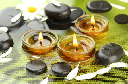 alternative medicine: spa stones with flowers and candles in water on plate