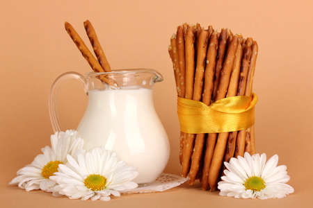 Tasty crispy sticks with pitcher with sour cream on beige background photo