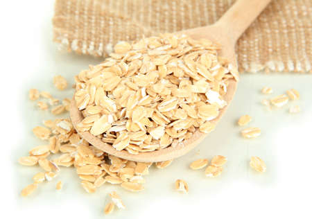 close up of oat flakes in wooden spoon  isolated on white photo