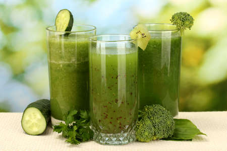 Three kinds of green juice on bright background photo