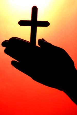 simbolos religiosos: las manos del hombre con crucifijo, sobre fondo rojo Foto de archivo