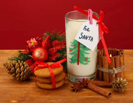 Cookies for Santa: Conceptual image of ginger cookies, milk and christmas decoration on red background Stock Photo - 17215119