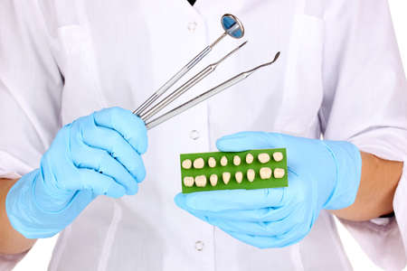 dentists hands in blue medical gloves with dental tools and denture photo