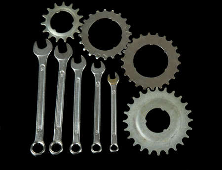 Metal cogwheels and spanners isolated on black photo