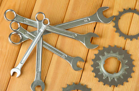 Metal cogwheels and spanners on wooden background photo