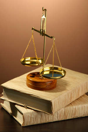 Gold scales of justice and books on brown background Stock Photo - 17214737