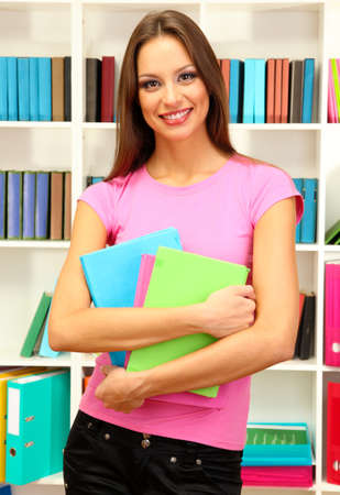 Young attractive female student holding her school books in library Stock Photo - 17263173