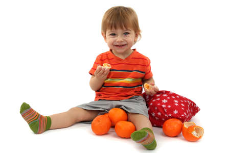 cute little boy eating tangerines, isolated on white photo